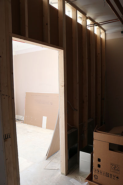 A picture of interior framing with construction materials ready to be cut to size and installed.