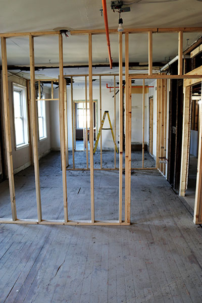 A view through the walls of three different apartment rooms before they are completely insulated and walled in.
